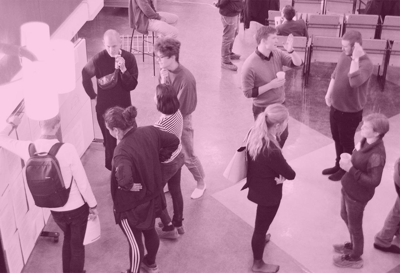 På bilden syns ett tiotal människor utspridda i små grupper på ett golv. Bilden är tagen uppifrån och har ett rosa filter.