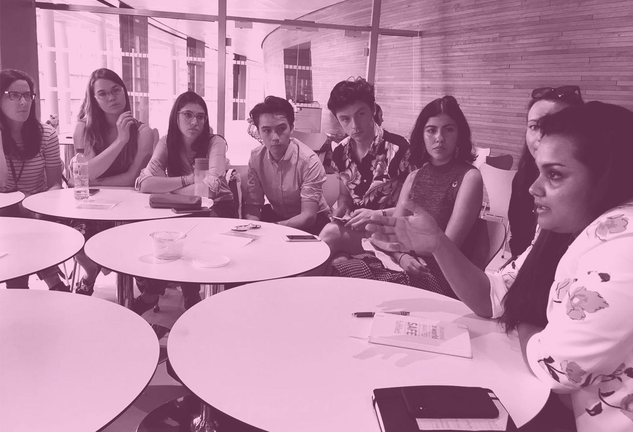 På bilden syns fem runda bord och åtta personer i samtal. Bilden har rosa filter