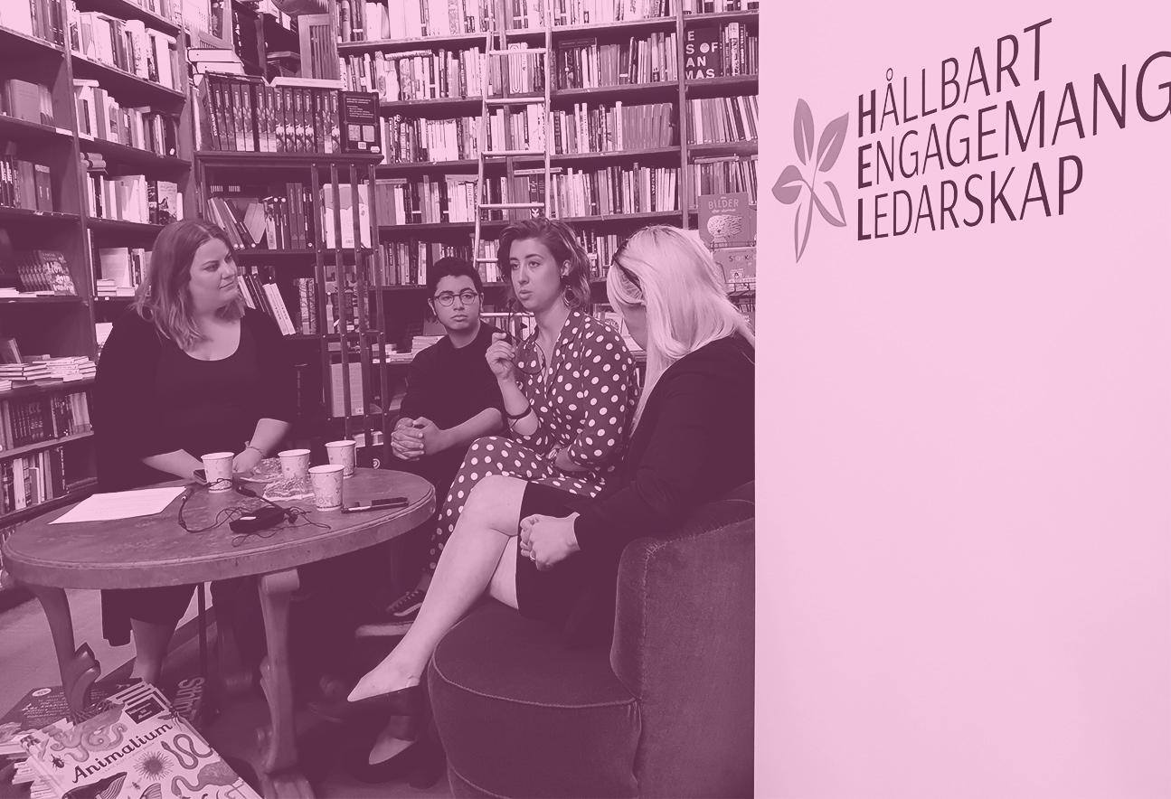 På bilden syns fyra personer i ett bibliotek. Framför dom står ett bord med koppar. En rollup med HELs logotyp syns i förgrunden. Bilden har rosa filter