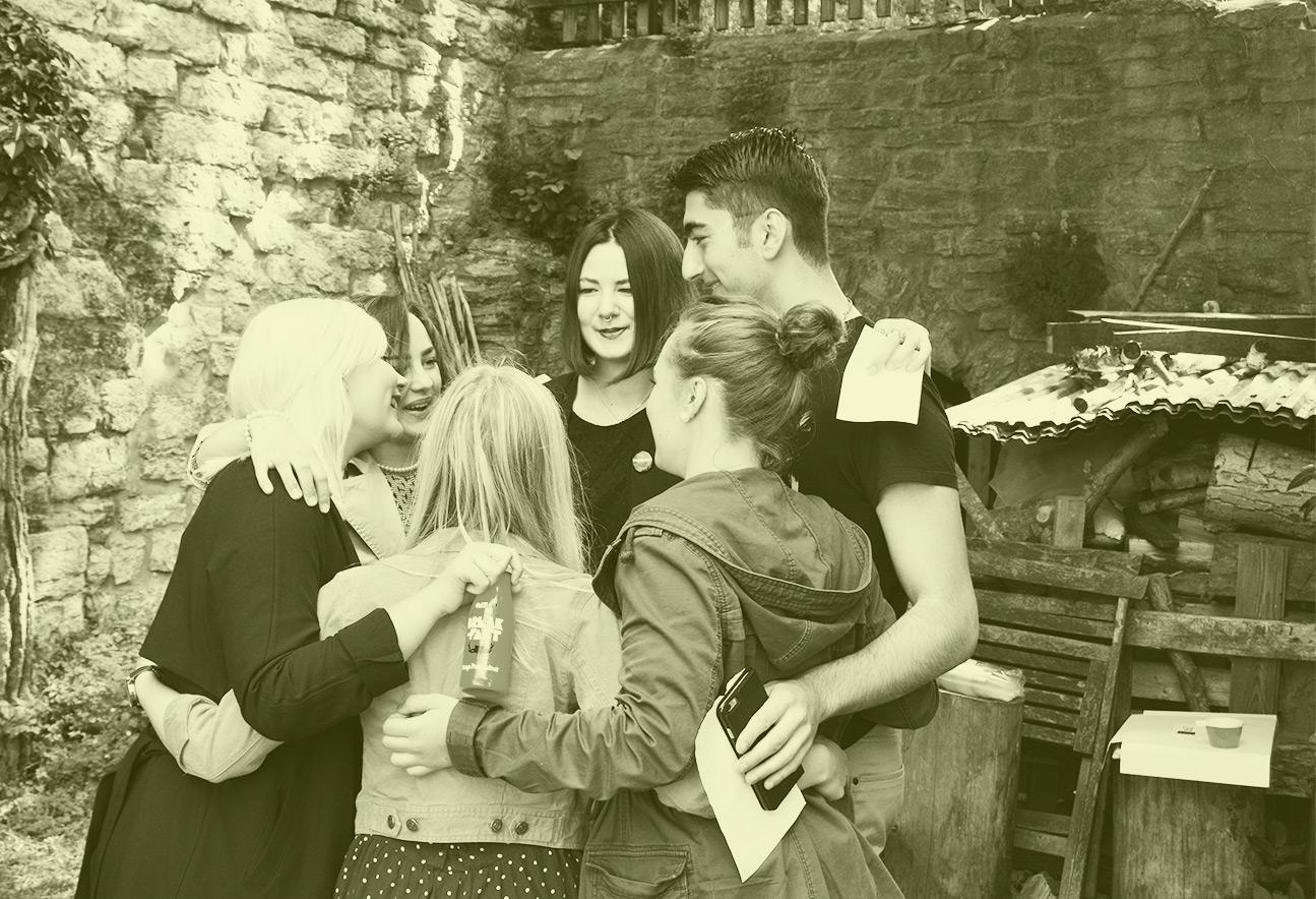 Sex personer står i ring och håller om varandra. Bilden har ett grönt filter.
