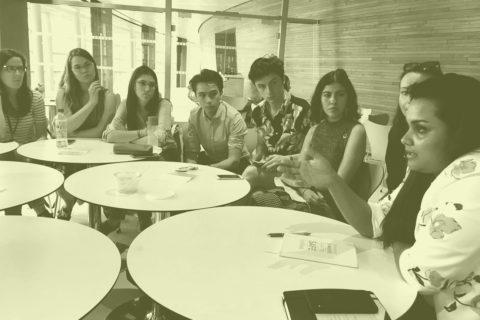 På bilden syns fem runda bord och åtta personer i samtal. Bilden har grönt filter